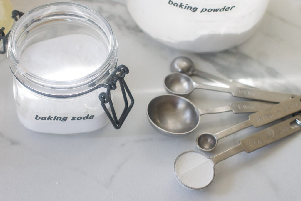 baking powder and baking soda in jars on a counter next to measuring spoons