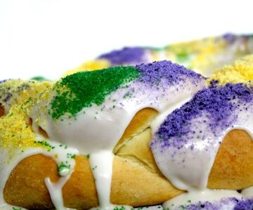 Mardi Gras King Cake: Braided brioche bread frosted with white royal icing and decorated with purple, green and gold sugar.