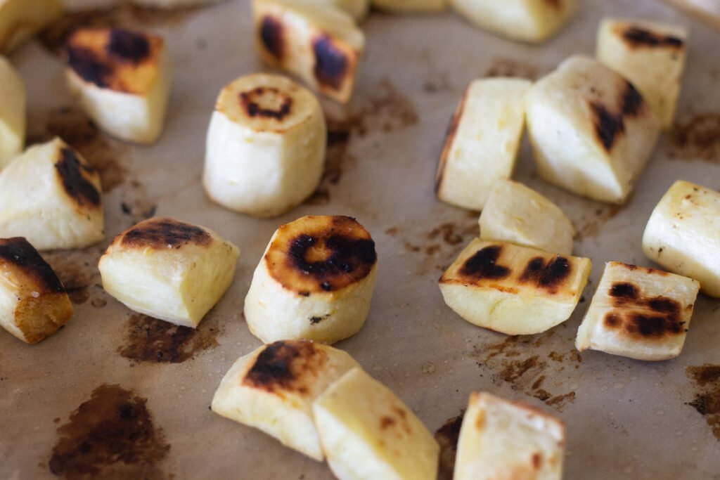 Pieces of roasted parsnip on sheet pan.