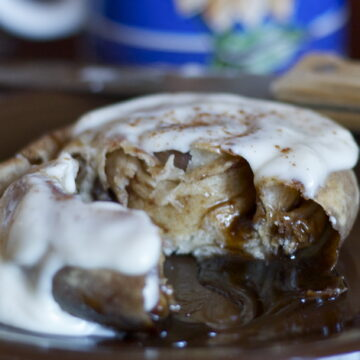Baked quick and easy cinnamon roll on brown plate.