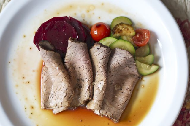 Roast beef dinner on white plate with jus.