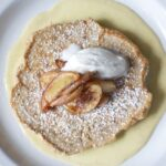 Caramelized apple pancakes with creme anglaise on plate.