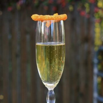 Champagne in glass with Cheetos on top.