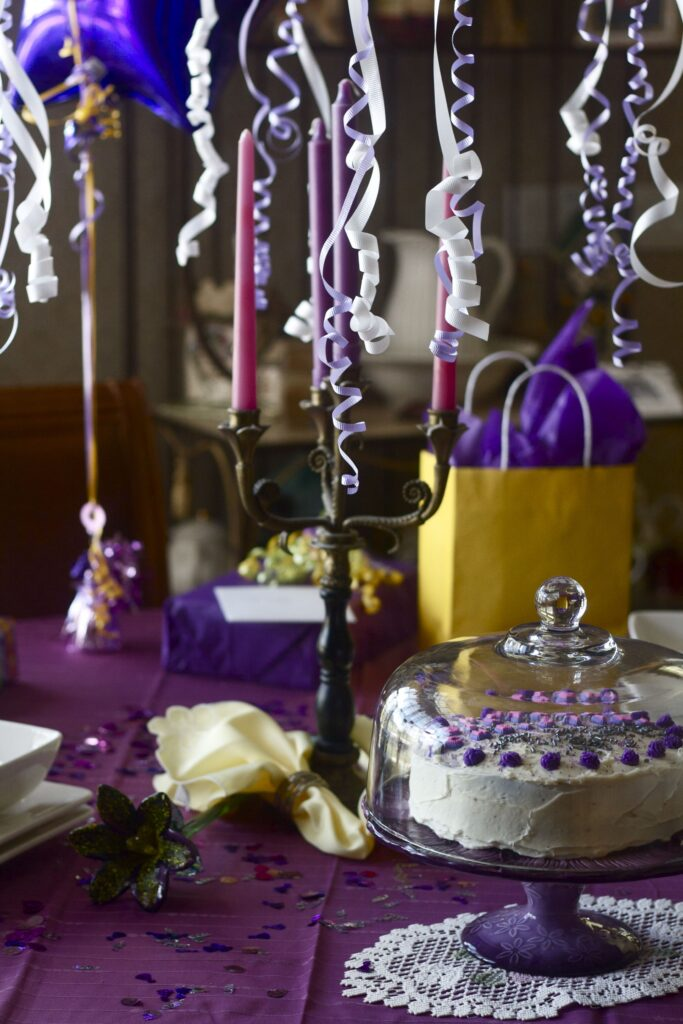 Ribbon hanging from light fixture over candelabra and birthday cake.