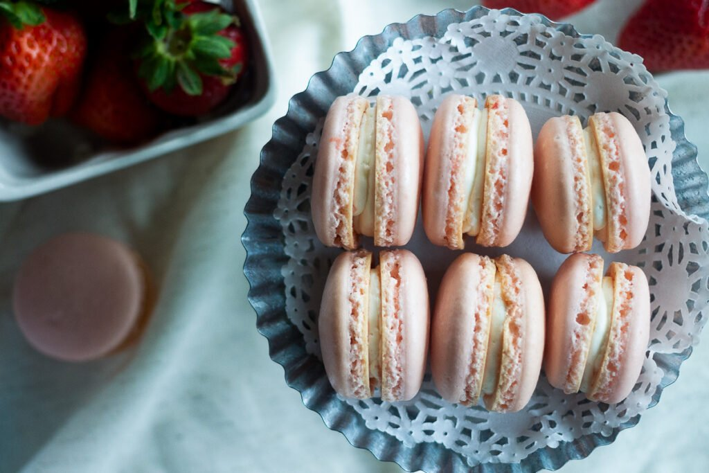 Strawberry macarons with vanilla buttercream filling on mini silver cake plate lined with doily.