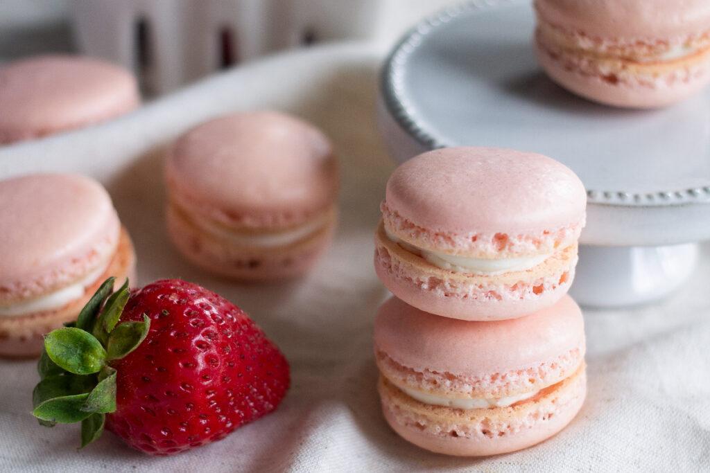 Strawberry French macarons stacked on white linen napkin next to fresh strawberry.