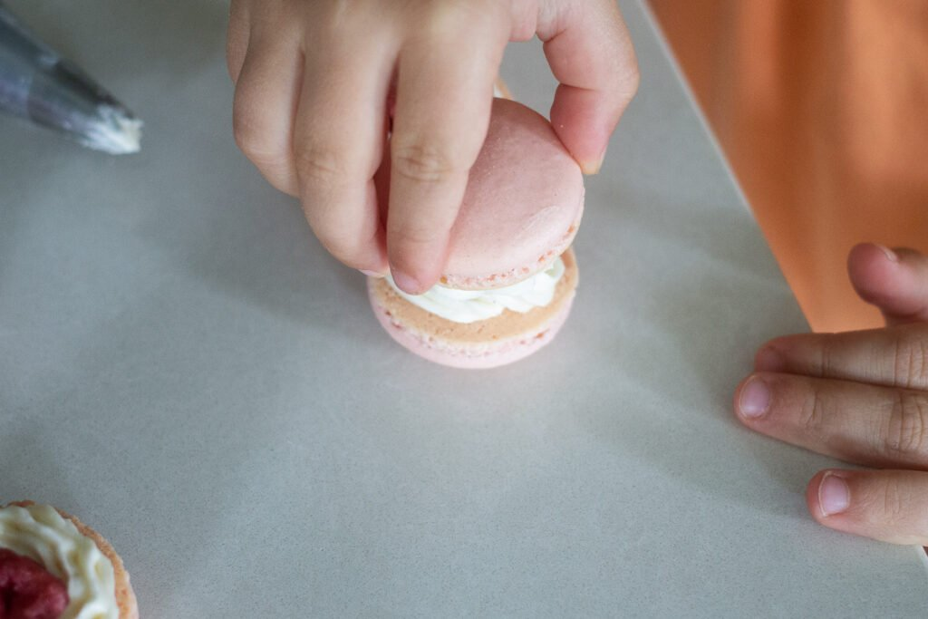 Child's hands placing one strawberry macaron shell on top of another with piped vanilla buttercream