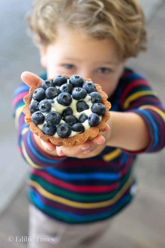 Little boy holding up fresh fruit tart.