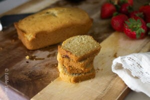 Lemon pound cake slices stacked on cutting board with strawberries