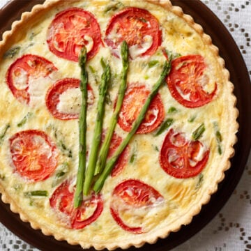Tomato and asparagus quiche on plate.