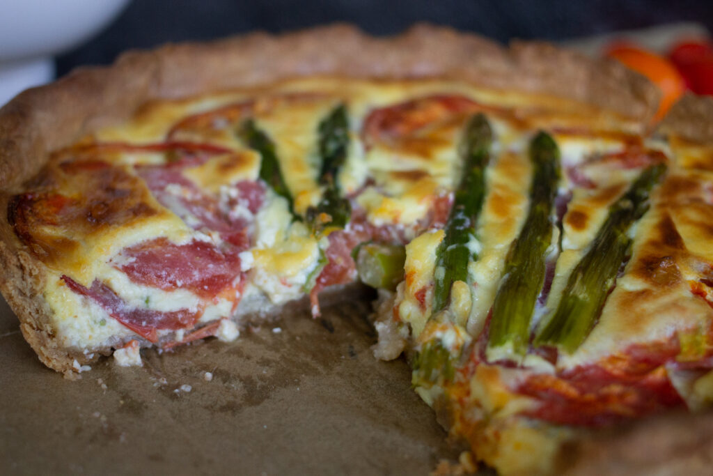 Asparagus and tomato quiche with slice removed from Edible Times