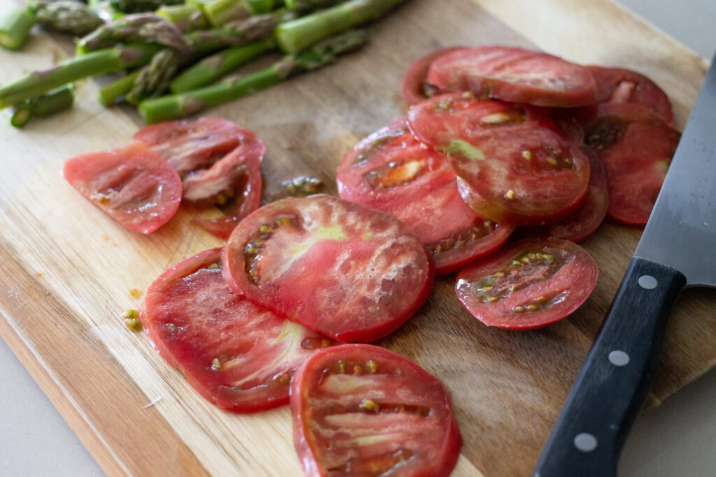 Sliced tomatoes on cutting board with asparagus.