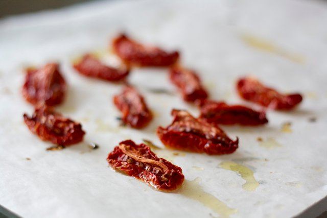 Oven-dried tomatoes on parchment paper.