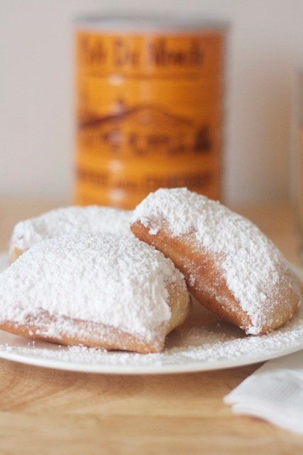 Beignets on plate with can of coffee in background.