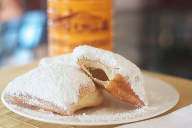 New Orleans beignets dusted with powdered sugar on plate.