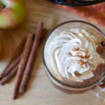 Apple cider topped with whipped cream, on counter with cinnamon sticks and apples.