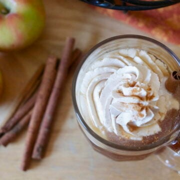 Easy homemade apple cider topped with whipped cream, on counter with cinnamon sticks and apples.