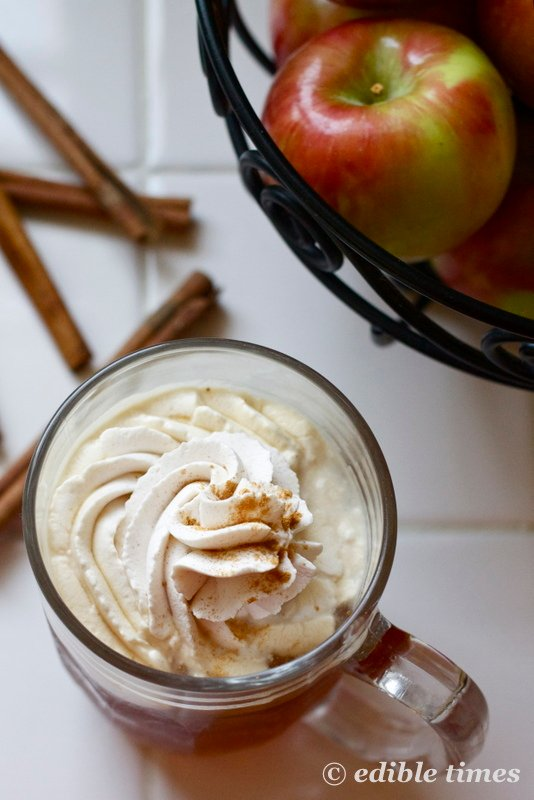 Apple cider topped with whipped cream in mug, on counter next to basket of apples.