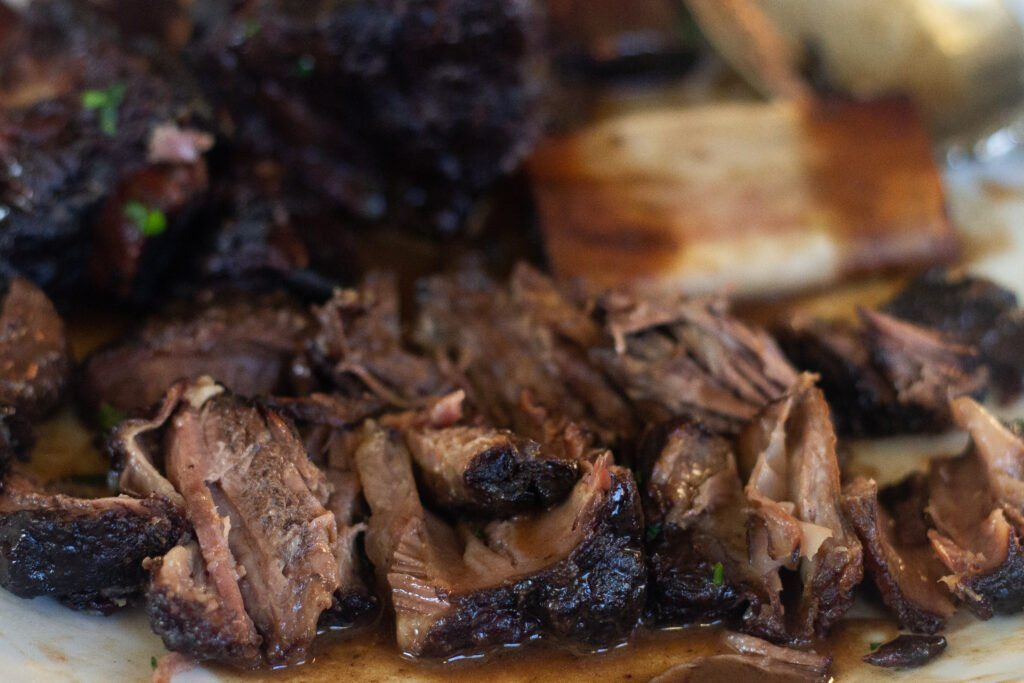 Close-up of beef short ribs pulled from the bone on a plate with braising sauce