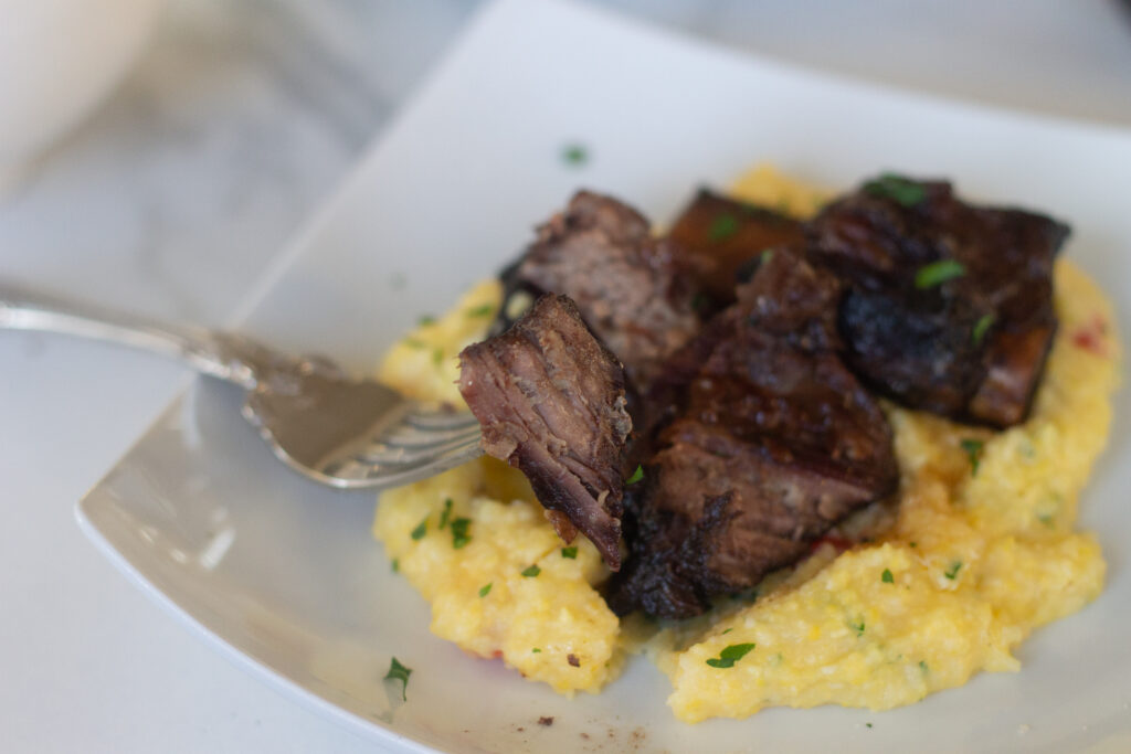 Short ribs braised in wine on plate over a bed of herbed Parmesan polenta.