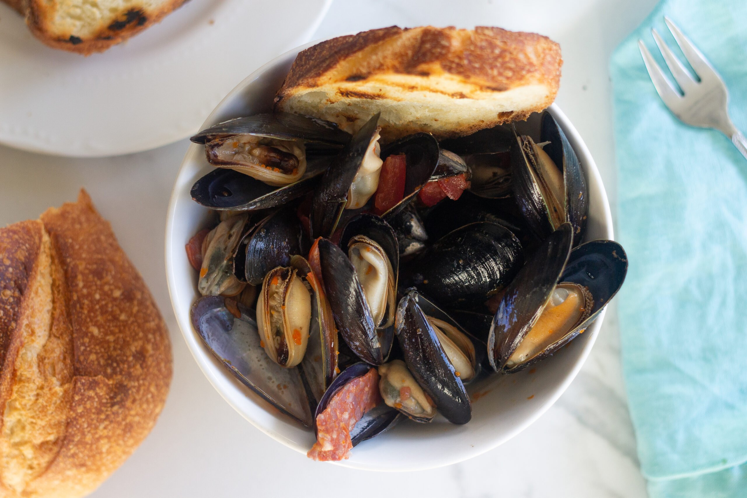 Steamed mussles in a bowl with crusty baguette.