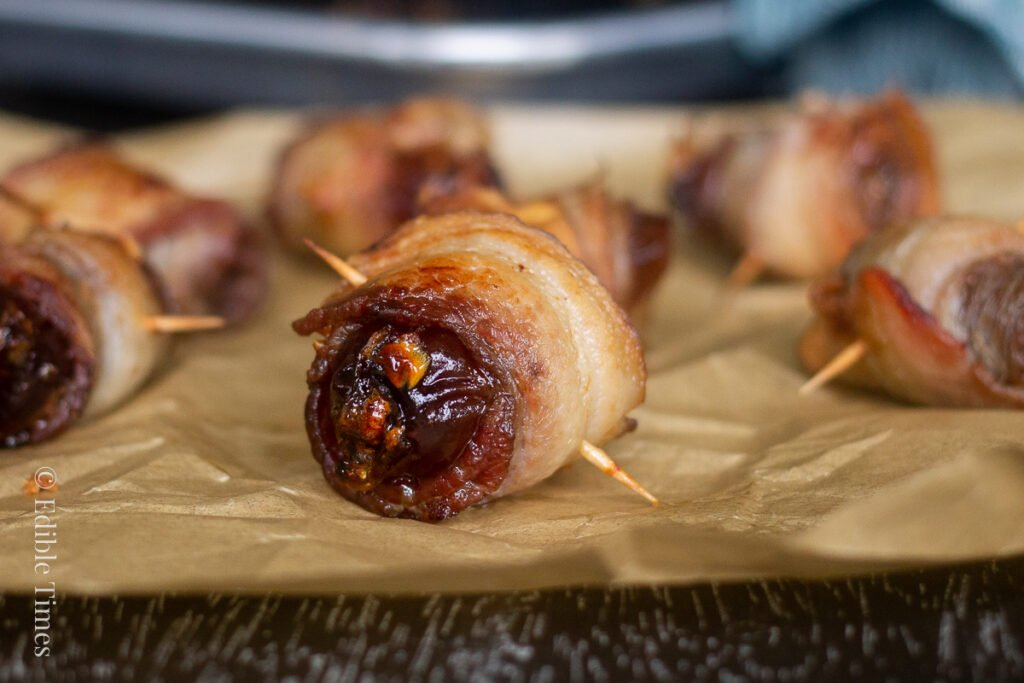 Bacon wrapped stuffed date on parchment paper.