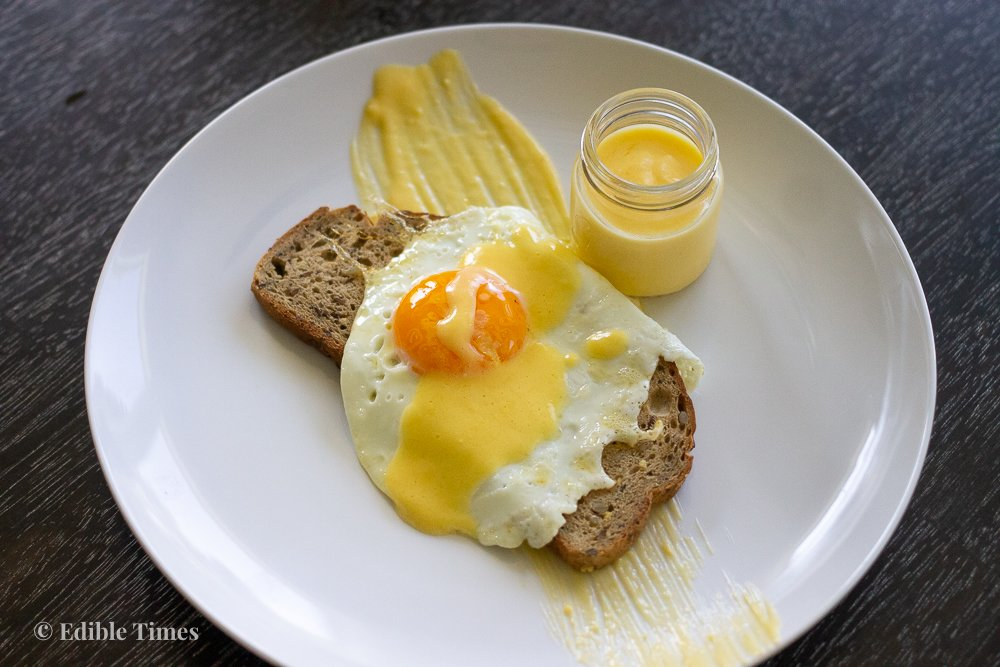 Fried egg on toast with hollandaise sauce drizzled on top and in shot glass.