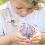Child sipping homemade blueberry soda through a straw in backyard,