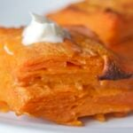 Sweet potato gratin on plate with creme fraiche on top.