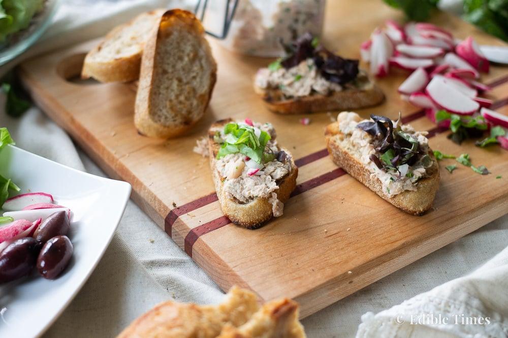 Close up of mini tuna tartines on cutting board.
