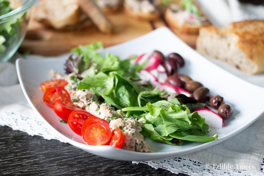 Tuna niçoise salad on sloped square plate on table.