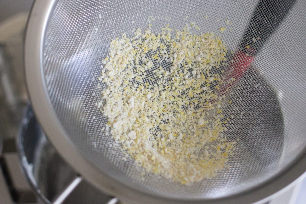 Sifting macaron dry ingredients with lemon zest on Edible Times