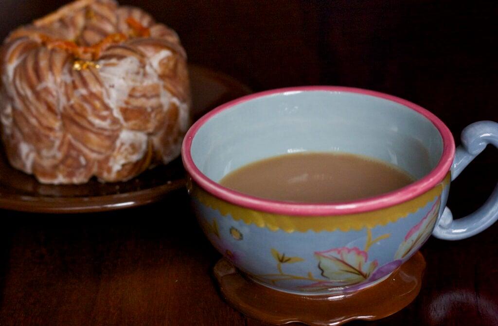 Brewed fair trade coffee in mug, next to cronut.