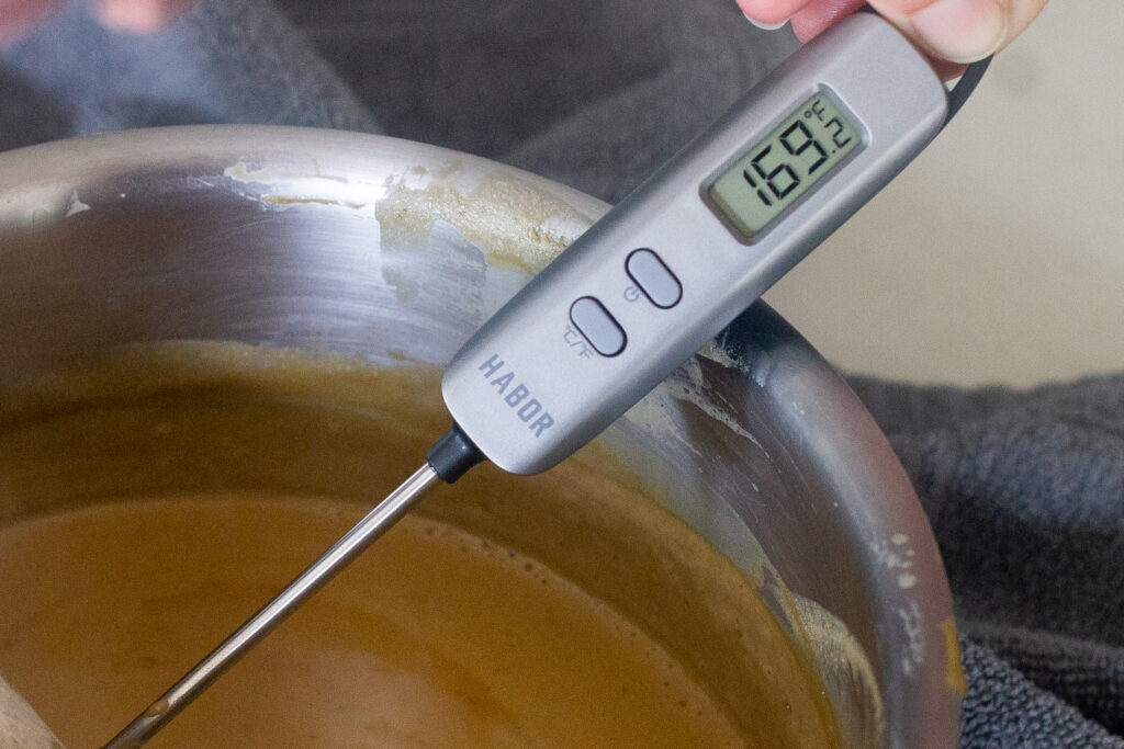 Meat thermometer with temperature of cooked custard in pot.