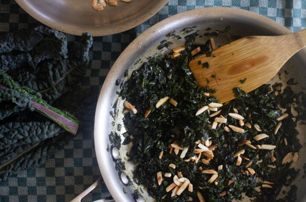 Kale sauteeing in a pan with almonds