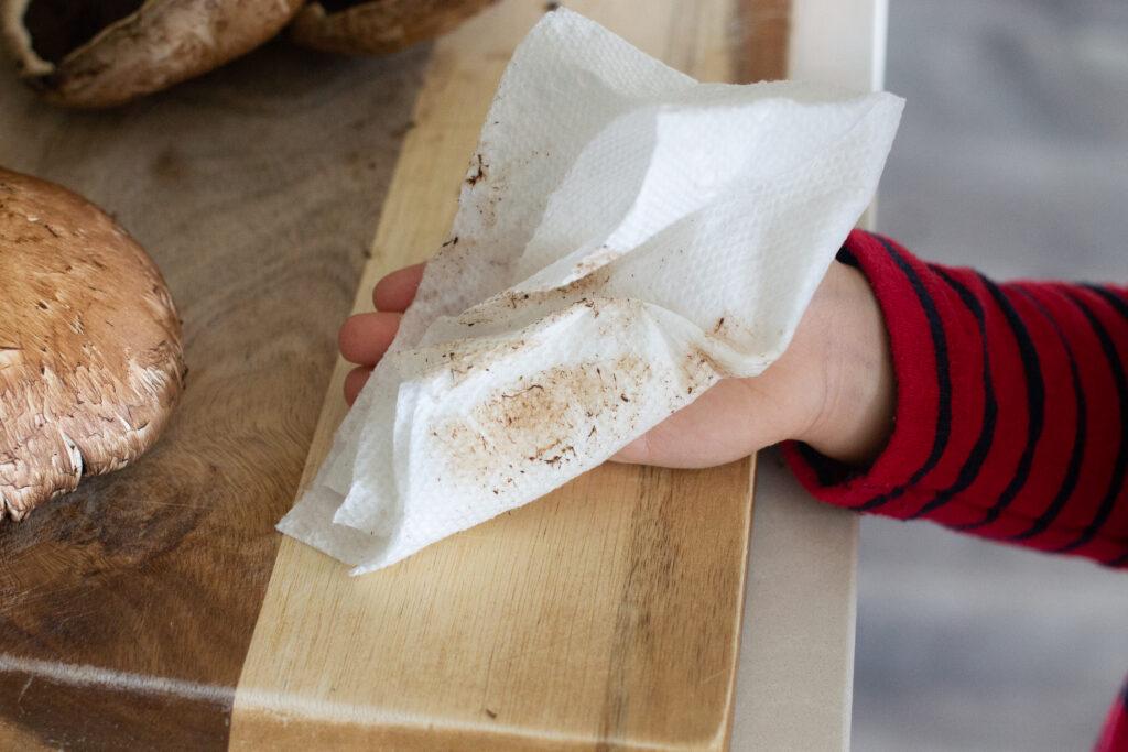 Child cleaning top of portobello mushroom.
