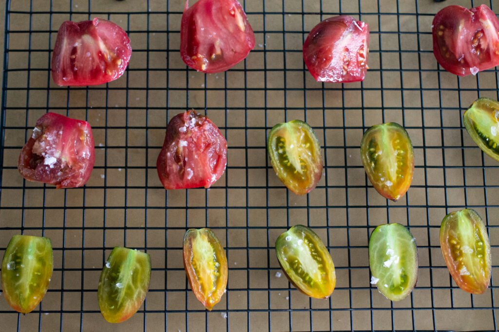 Sliced tomatoes on drying rack.