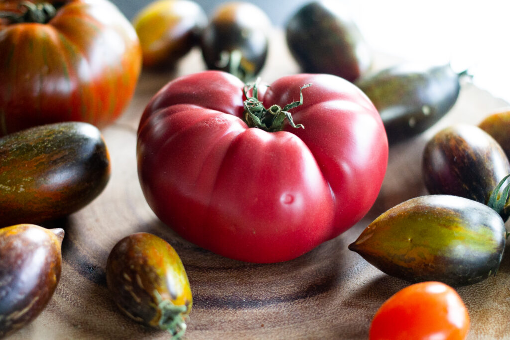 Heirloom tomatoes on a wooden stump.