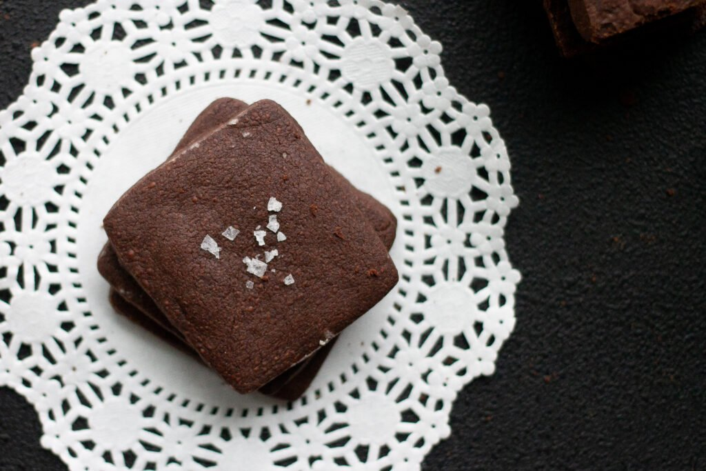 Chocolate shortbread cookies with sea salt on lace doily.