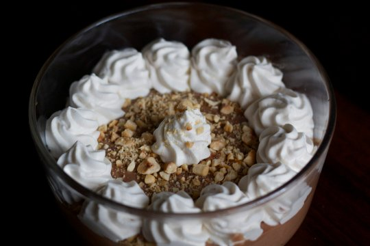 Dessert dip with Nutella, whipped cream and crushed hazelnuts in bowl.