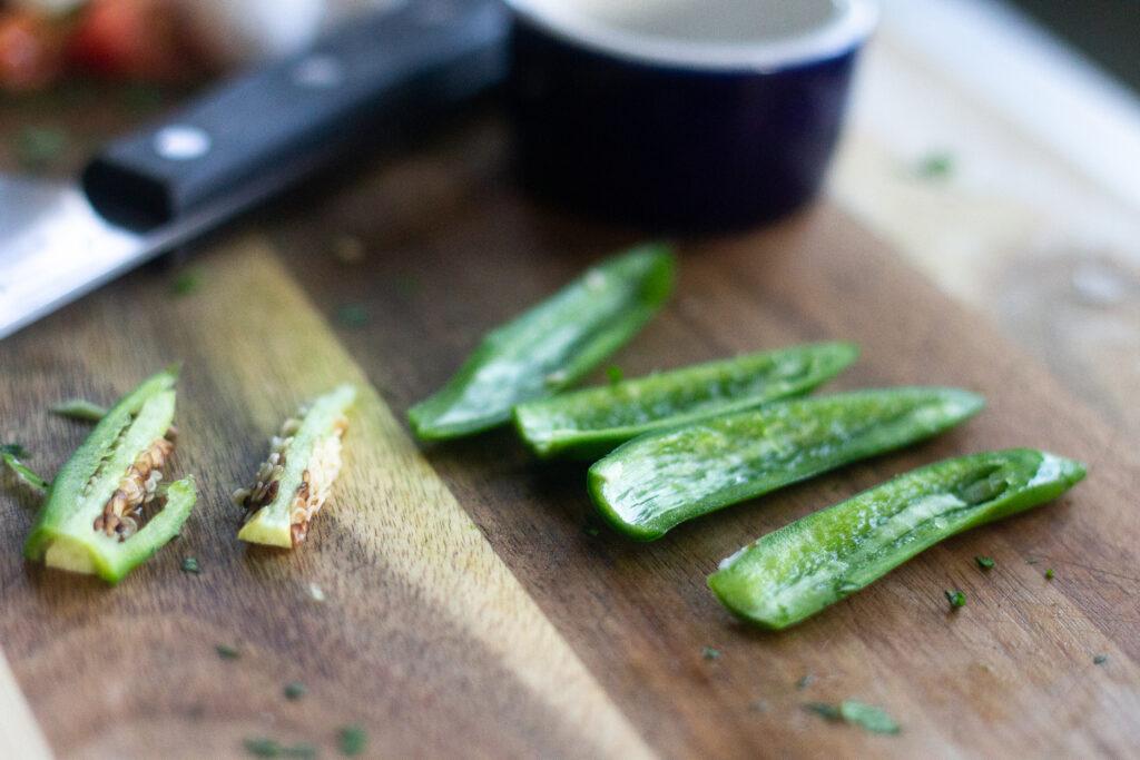 Serrano chilis, seeds removed, on cutting board for pico de gallo.