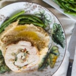Stuffed pork loin roulade on plate with parsnip purée and green beans.