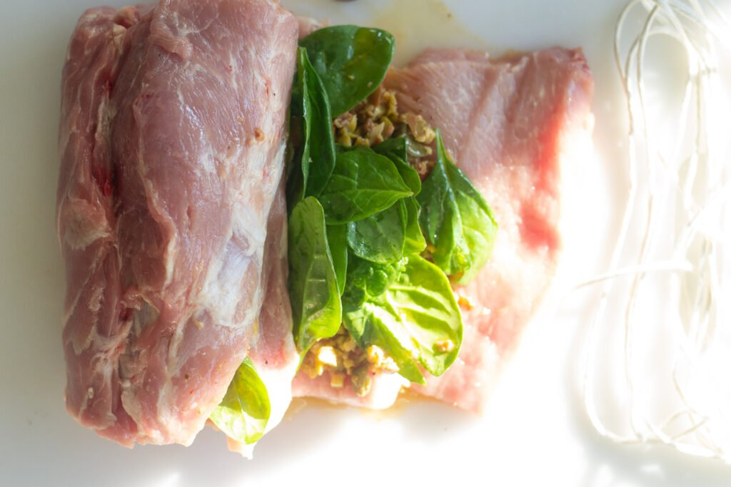 Rolling up stuffed pork loin with olives and spinach.