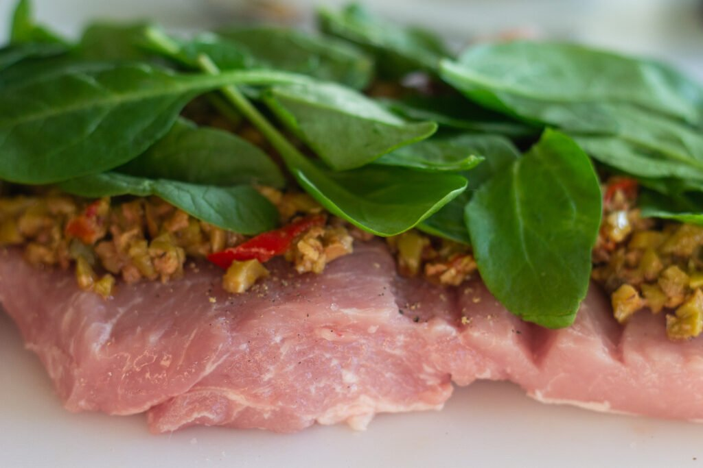 Raw, butterflied pork loin with olives and spinach on top.