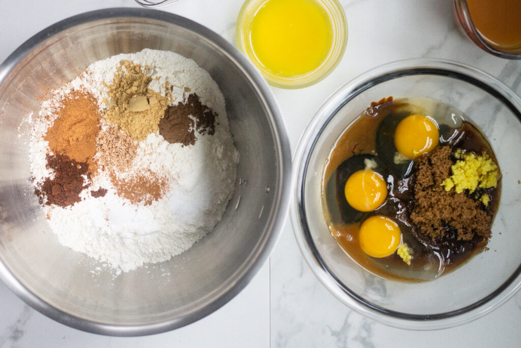 Two mixing bowls on counter, one with dry ingredients, the other with wet for gingerbread. And small glass container of melted butter.