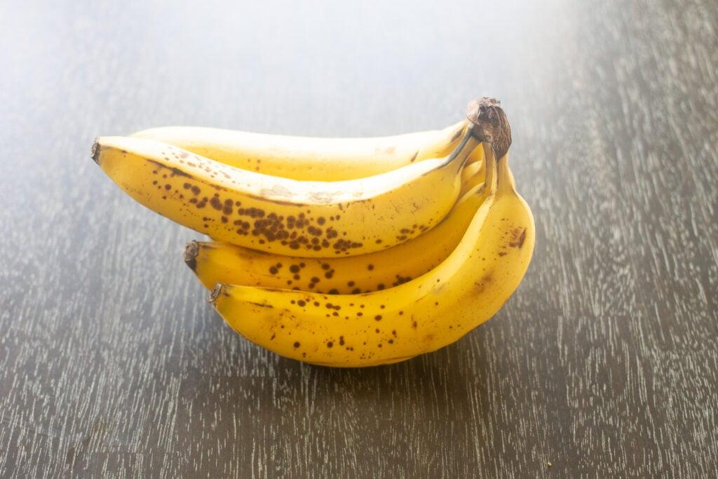 Ripe bananas on dark wooden table.