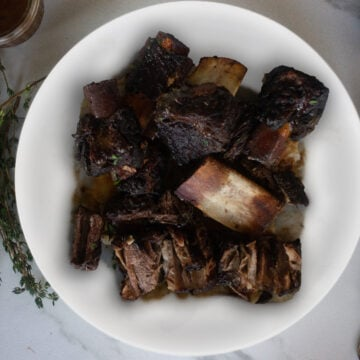 Braised beef short ribs on plate with fresh thyme garnish.