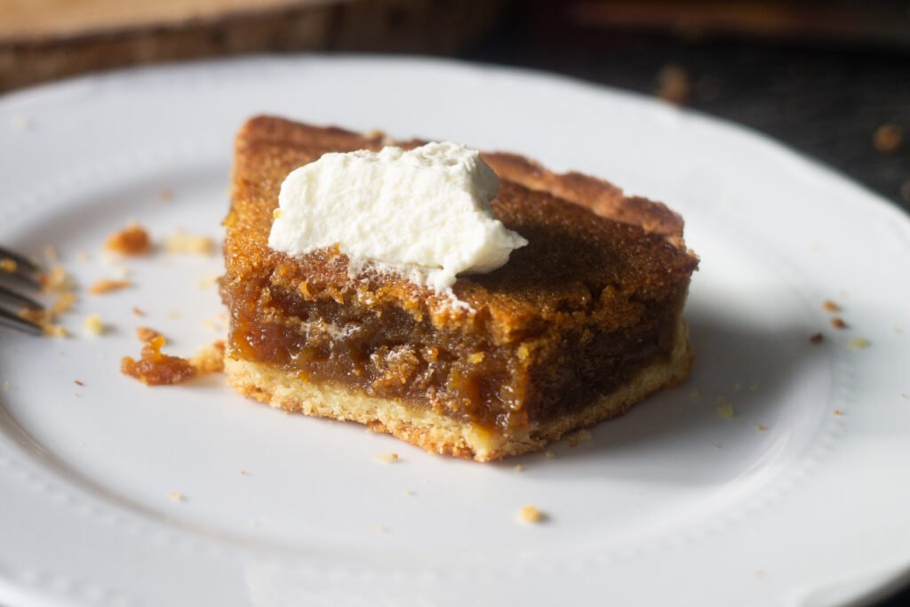 Half eaten treacle tart on white plate.