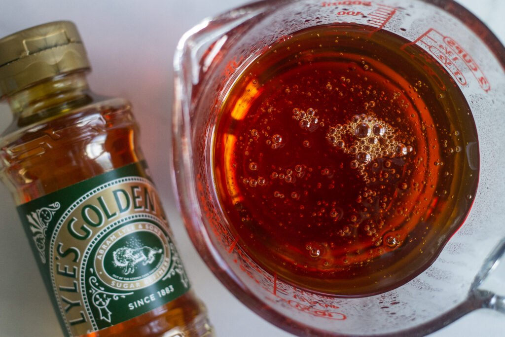 Lyle'S Golden Syrup in glass measuring cup next to bottle on the counter.