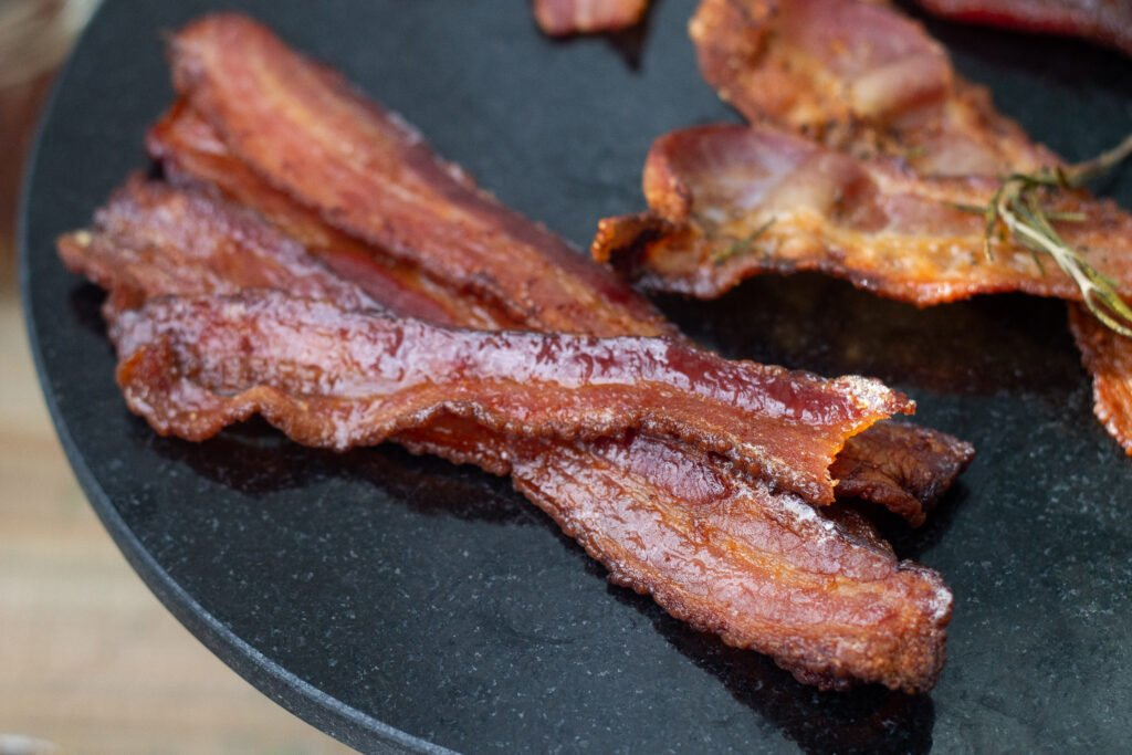 Bacon cooked in the oven, on a black round plate.